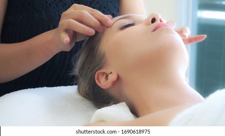 Relaxed woman lying on spa bed for facial and head massage spa treatment by massage therapist in a luxury spa resort. Wellness, stress relief and rejuvenation concept.