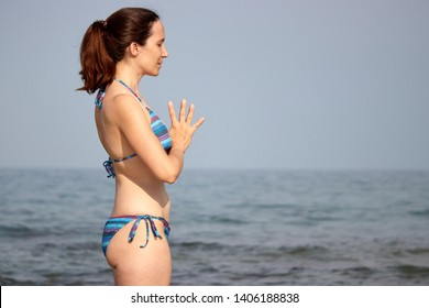 relaxed woman on the beach doing the anjali mudra, prayer greeting in yoga