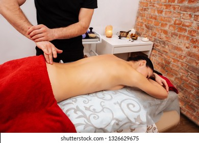 Relaxed woman . Precious active masseur pressing on coccyx of his female client while she chilling on massage table