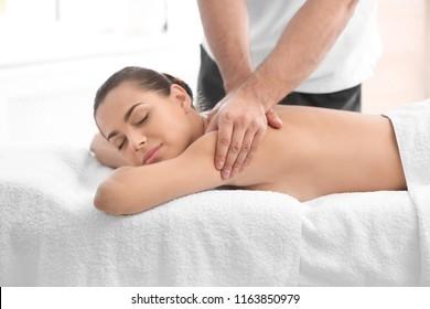 Relaxed woman receiving back massage in wellness center