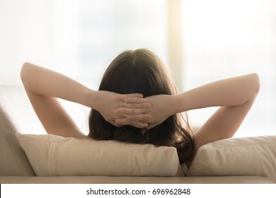 Relaxed woman resting on sofa hands behind head, breathing fresh air, enjoying peaceful moment, feeling no stress, relaxing on comfortable couch at home, practicing yoga and meditation, back view