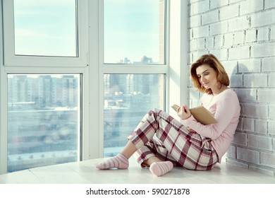 relaxed woman sitting on a floor near a window with a book. girl reading at home