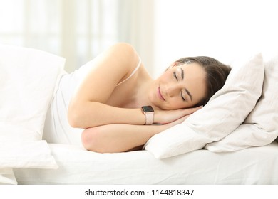 Relaxed woman sleeping lying on the bed wearing a smartwatch at home