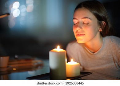 Relaxed woman smelling a lighted scented candle in the night at home