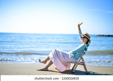 relaxed woman in straw hat in chaise longue at the sea watching the blue horizon. peaceful and tranquil mood at sunset