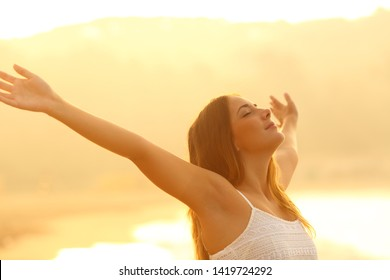 Relaxed woman stretching arms breathing deep fresh air at sunset on the beach