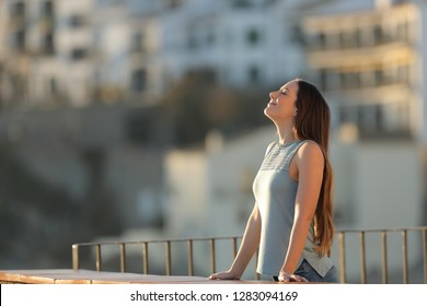 Relaxed woman in a town breathing fresh air from a rural apartment balcony