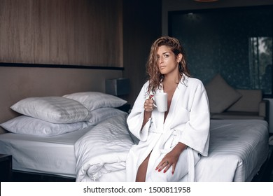 Relaxed woman with wet blond wavy hair, wearing white bathrobe. The woman sits on her bed drinking tea from the white mug; atmosphere concept.