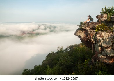 Relaxed women seated on cliff and enjoying landscape view with camera. Beautiful mist and light blue sky backgrounds. Thai-Laos border. Na Haeo, Loei, Thailand. Winter season. Bright morning light.