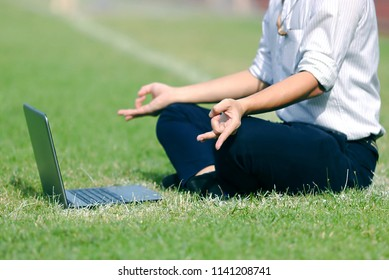 Relaxed young Asian business man with laptop doing yoga position on the field.