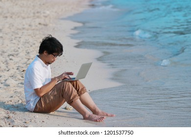 Relaxed young Asian man with laptop sitting on sandy of the beach. Internet of things concept.