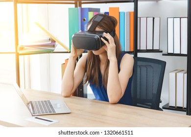 Relaxed young Asian woman wearing virtual VR reality glasses on workplace in office.