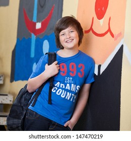 Relaxed young boy with his school books slung over his shoulder in a bag leaning against a brightly colored wall with graffiti