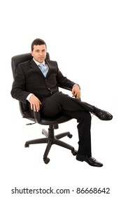 Relaxed young business man sits on office chair over white background