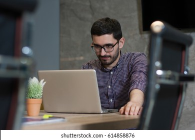 Relaxed young business owner is working at his desk on his laptop