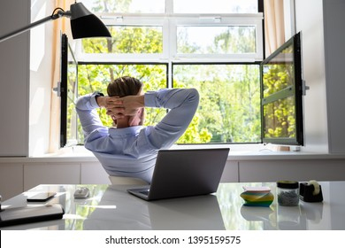 Relaxed Young Businessman Relaxing On Chair Behind Desk At Office