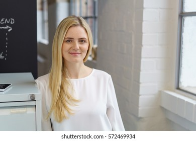 Relaxed young businesswoman with a sincere smile standing leaning against a filing cabinet in the office alongside large windows