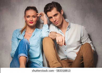 relaxed young casual couple sitting together and look at the camera in studio