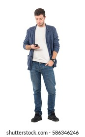 Relaxed young casual man in denim shirt and jeans typing message on cellular phone. Full body length portrait isolated over white background.