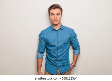 relaxed young casual man in jeans shirt standing with one hand in pocket against grey studio background