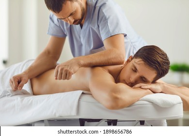 Relaxed young client lying on massage table with closed eyes enjoying remedial body massage done by professional masseur in modern spa salon or wellness center