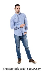 Relaxed young corporate man holding mobile phone looking at camera. Full body length portrait isolated over white background.