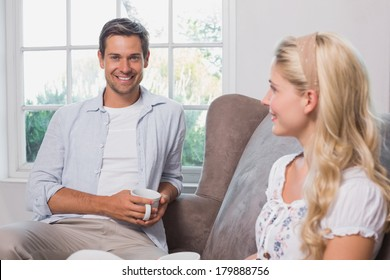 Relaxed young couple with coffee cups sitting in living room at home