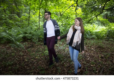 Relaxed young couple holding hands while walking through forest. Caucasian lifestyle concept.