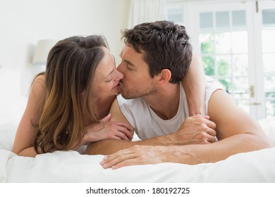 Relaxed young couple kissing in bed at home