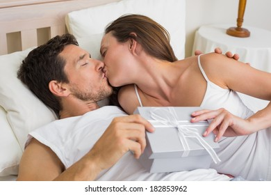 Relaxed young couple kissing with gift box in hand in bed at home