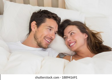Relaxed young couple lying together in bed at home