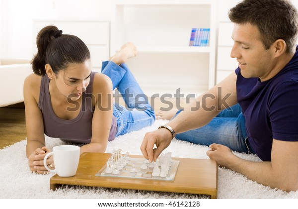 Relaxed young couple playing chess at home lying on floor.