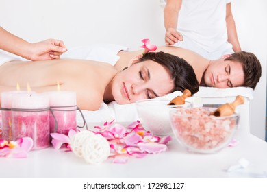 Relaxed Young Couple Receiving An Acupuncture Treatment In A Spa Center