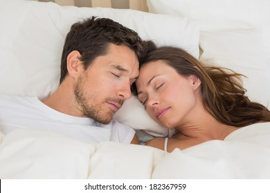 Relaxed young couple sleeping together in bed at home