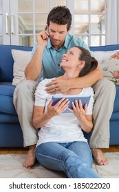 Relaxed young couple using digital tablet and cellphone in the living room at home