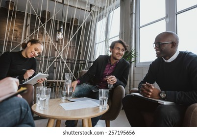 Relaxed young executives having a meeting indoors. Multiracial group of people sitting in office lobby discussing business.