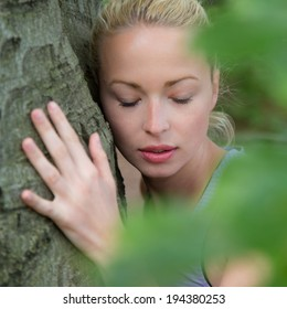 Relaxed young lady embracing a tree receiving life energy from the nature.