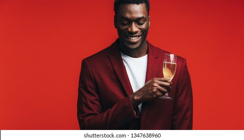 Relaxed young man with a glass of champagne and thinking against colored background. Man remembering a special moment while having a glass of champagne.