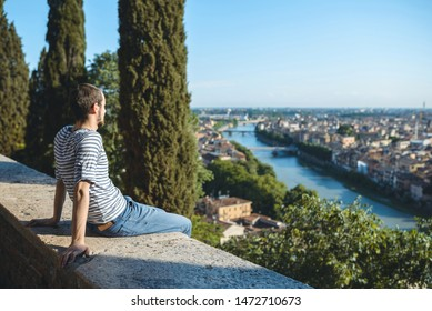 relaxed young man looking at river and city in italy