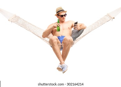 Relaxed young man lying in a hammock with a beer in his hand and typing on his cell phone isolated on white background