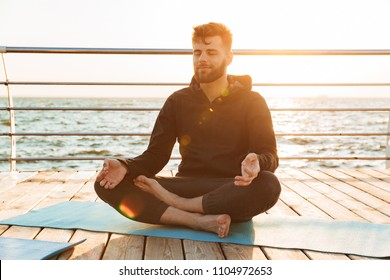 Relaxed young man meditating while sitting on a fitness mat at the beach