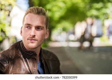 Relaxed young man sitting down on a bench outdoors wearing a brown leather jacket looking away. Sunny summer day.