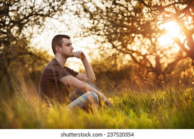 Relaxed young man sitting in grass in autumn