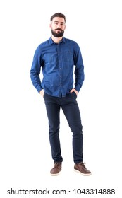 Relaxed young man wearing blue denim shirt with hands in pockets looking at camera. Full body isolated on white background.