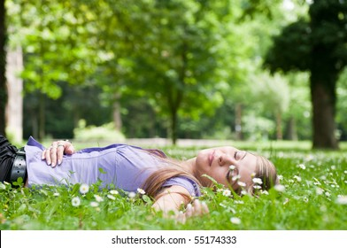Relaxed young person (teenage girl) lying in grass and flowers with stretched hand - closed eyes