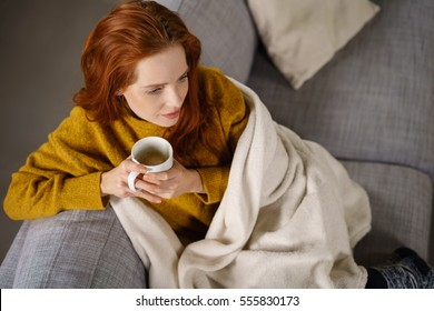 Relaxed young redhead woman enjoying a tea break sitting wrapped in a warm blanket on a comfortable couch staring thoughtfully ahead, high angle view