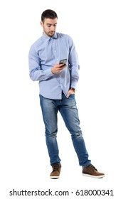 Relaxed young smart casual business man typing message on mobile phone. Full body length portrait isolated over white background.