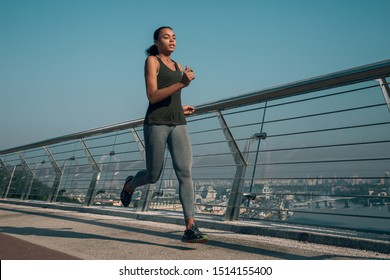 Relaxed young sportswoman looking calm while jogging on the bridge