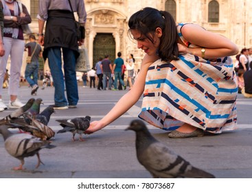relaxed young woman in colorful dress feeds the pigeon on lively square in front of Dome of Milano