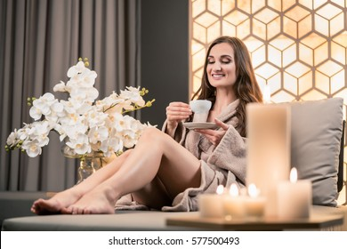 Relaxed young woman drinking herbal tea while sitting on sofa before spa treatment in wellness center